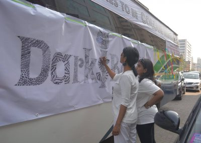 Volunteers and supporters doodling anti-colourist messages on the petition bus.